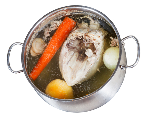 boiling of chicken broth with seasoning vegetables in steel pan isolated on white background